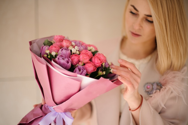 Ragazza nel cappotto guardando il bouquet di fiori viola e rosa viola