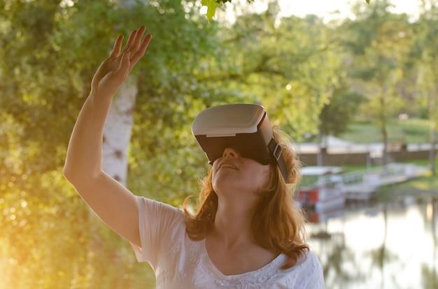 Ragazza nel casco della realtà virtuale contro la superficie della natura