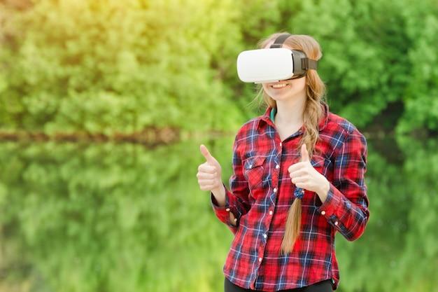 Ragazza nel casco della realtà virtuale sullo sfondo della natura. mostra gesto cool