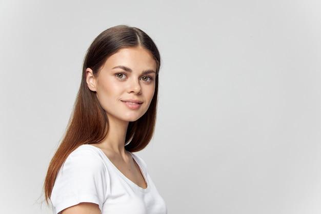 Ragazza nel modello di sorriso del brunette della maglietta bianca
