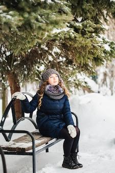 Ragazza nel parco di inverno coperto di neve
