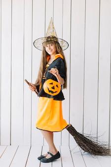 Ragazza nel volo di scopa di imitazione del costume di halloween in studio