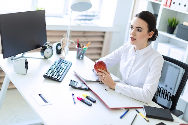 Ragazza nell'ufficio che lavora con i documenti e che tiene una mela.