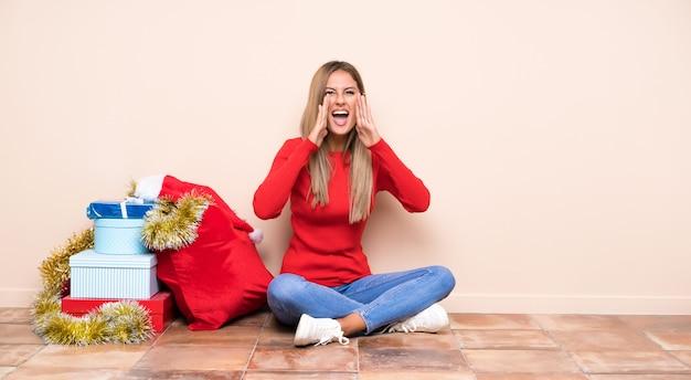 Ragazza nelle feste di natale che si siedono sul pavimento che grida con la bocca spalancata