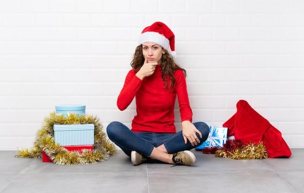 Ragazza nelle feste di natale che si siedono sul pavimento che pensa un'idea