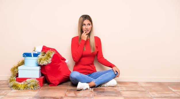 Ragazza nelle feste di natale che si siedono sul pavimento nervoso e spaventato