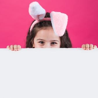Ragazza nelle orecchie del coniglietto che si nascondono dietro il tavolo
