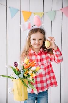 Ragazza nelle orecchie del coniglietto che tiene l'uovo di pasqua e fiori in annaffiatoio