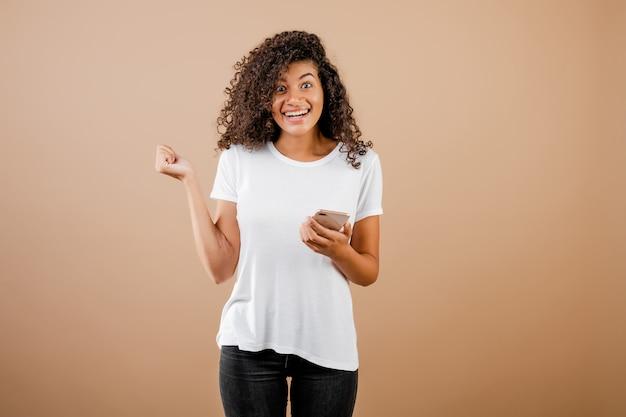Ragazza nera abbastanza giovane con il telefono a disposizione isolato sopra marrone