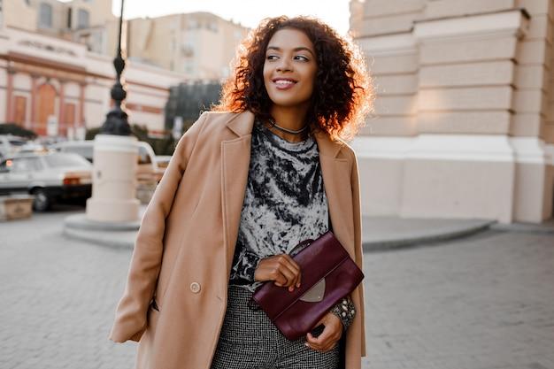 Ragazza nera alla moda in un fantastico maglione di velluto grigio, cappotto di lana beige, accessori di gioielli di lusso che camminano a parigi vicino al teatro.