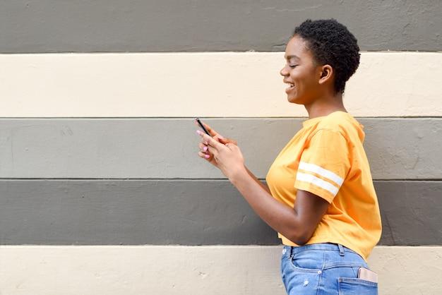 Ragazza nera che sorride e che per mezzo del suo smart phone all'aperto.