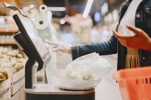 Ragazza nera con una maschera compra un cibo