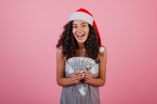 Ragazza nera felice che tiene cento banconote in dollari che portano il cappello di santa isolato