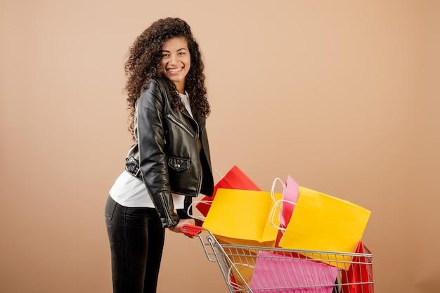 Ragazza nera felice con il carrello pieno delle borse variopinte isolate sopra marrone