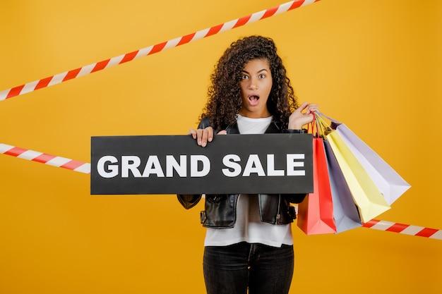 Ragazza nera felice con il grande segno di vendita e sacchetti della spesa variopinti isolati sopra giallo con nastro adesivo