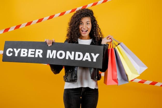 Ragazza nera sorridente con il segno cyber di lunedì e sacchetti della spesa variopinti isolati sopra giallo con nastro adesivo