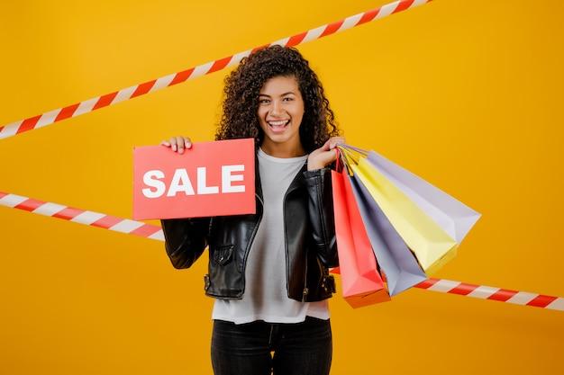Ragazza nera sorridente con il segno di vendita e sacchetti della spesa variopinti isolati sopra giallo con nastro adesivo