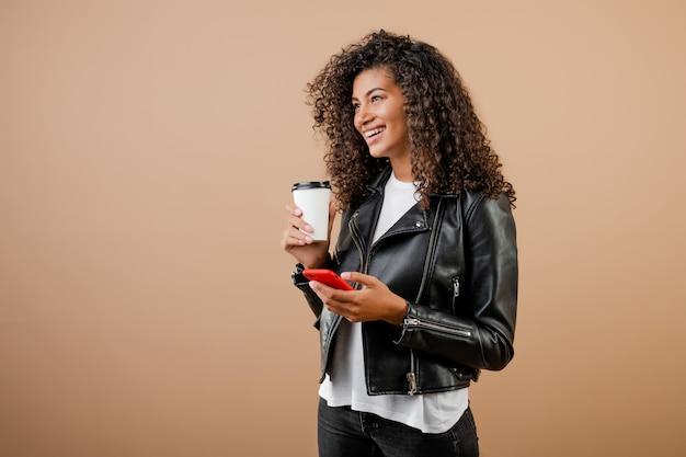 Ragazza nera sorridente felice con il telefono e il caffè per andare tazza isolata sopra marrone