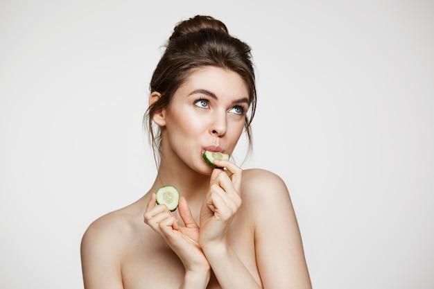 Ragazza nuda naturale abbastanza giovane con pelle pulita perfetta che mangia la fetta del cetriolo sopra fondo bianco. trattamento facciale.