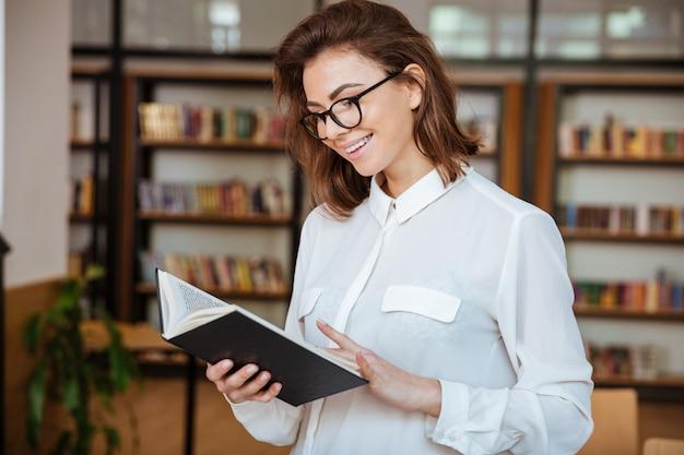 Ragazza o giovane donna felice dello studente in occhiali con il libro