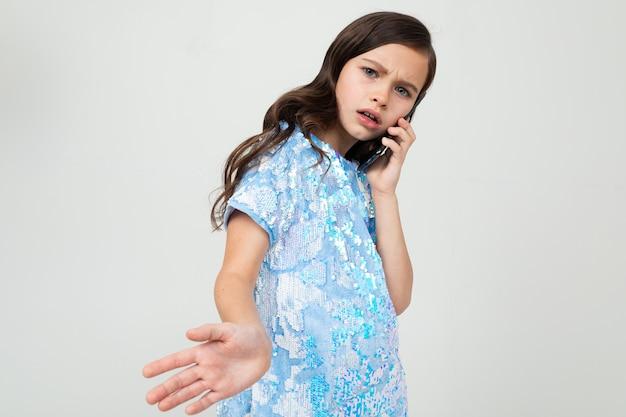 Ragazza onesta che parla con attenzione al telefono nell'interlocutore su un bianco