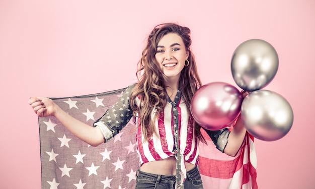 Ragazza patriottica con la bandiera dell'america su una parete colorata