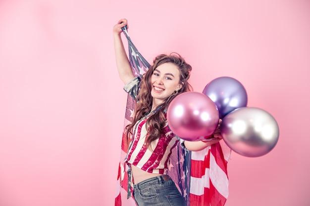 Ragazza patriottica con la bandiera dell'america su uno sfondo colorato
