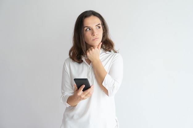Ragazza pensierosa che pensa sopra il messaggio di testo. giovane smartphone caucasico della tenuta della donna