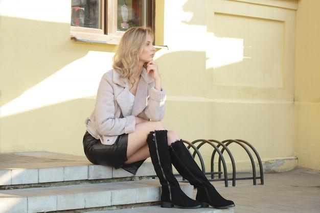 Ragazza pensierosa che si siede sulle scale nel giorno soleggiato di autunno