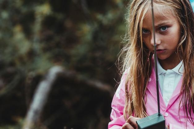 Ragazza persa nella foresta in una giornata piovosa, cercando di comunicare da gps con il suo telefono gps