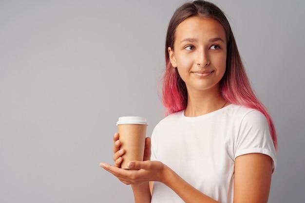 Ragazza piacevole dell'adolescente che tiene una tazza di caffè sopra un fondo grigio