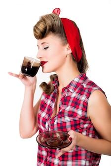 Ragazza pinup glamour in possesso di una tazza di caffè o tè caldo