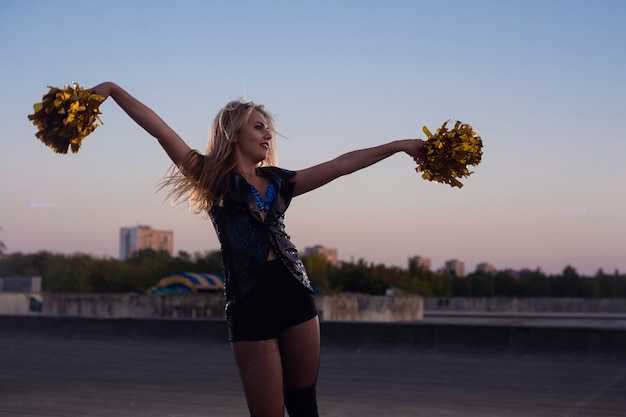 Ragazza pon pon con i pompon che ballano all'aperto sul tetto al tramonto