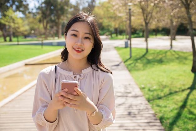 Ragazza positiva allegra con il cellulare che posa all'aperto