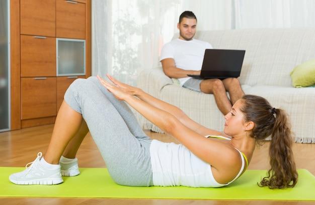 Ragazza praticando fitness e riposo fidanzato