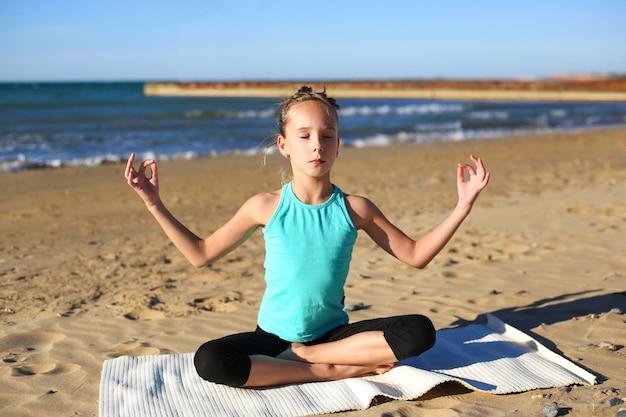 Ragazza praticando yoga sulla spiaggia.