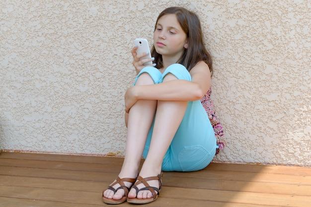 Ragazza pre dell'adolescente che manda un sms sul telefono cellulare