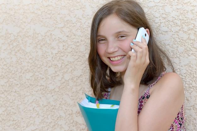 Ragazza pre dell'adolescente sorridente che rivolge allo smartphone, all'aperto