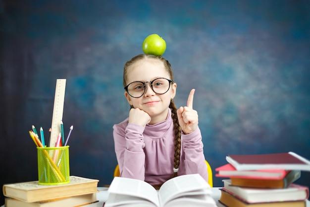 Ragazza premurosa della scuola elementare con la mela su aead che ha un'idea