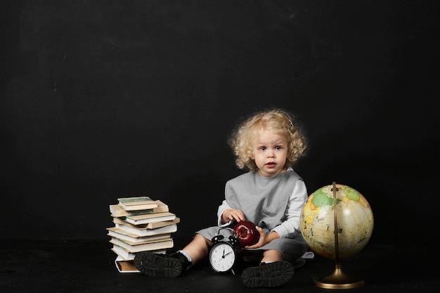 Ragazza prescolare felice con libri, un globo e un orologio su un fondo nero