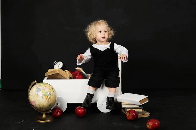 Ragazza prescolare felice vicino al carrello con libri, un globo e un orologio su un fondo nero