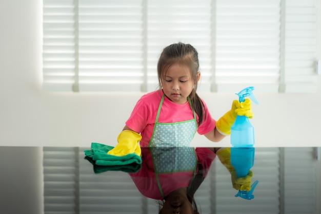 Ragazza prescolare sveglia asiatica dello studente che lava tavola di vetro con l'asciugamano verde in salone a casa, con spruzzo della soluzione detergente e dell'acqua.