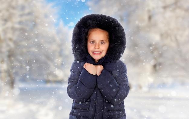 Ragazza protetta con cappotto nero in una giornata fredda e nevicata