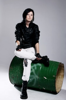 Ragazza punk che si siede sul barilotto di metallo