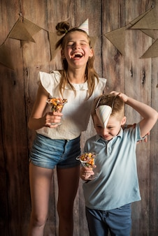 Ragazza, ragazzo che divide mangiando popcorn in una ciotola su un fondo di tavolo in legno. concetto di condivisione.