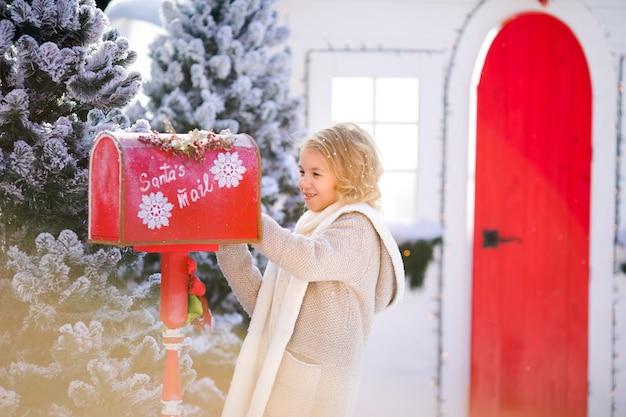 Ragazza riccia bionda sorridente con la lettera vicino alla cassetta delle lettere di santa