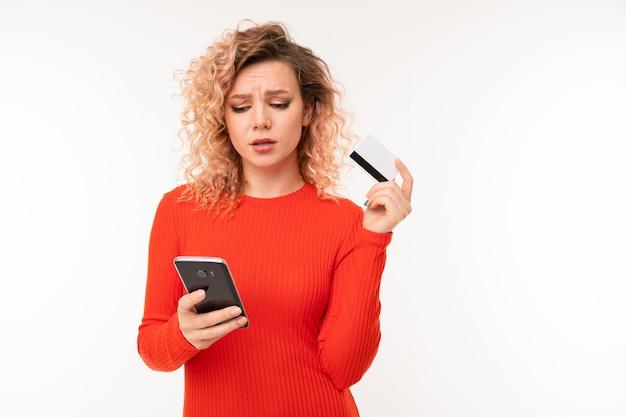 Ragazza riccia con il telefono e la carta di credito contro la parete bianca dello studio