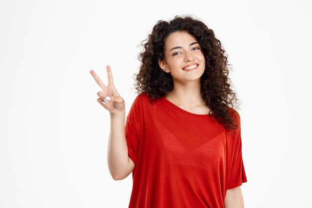 Ragazza riccia tenera che sorride e che mostra gesto di pace