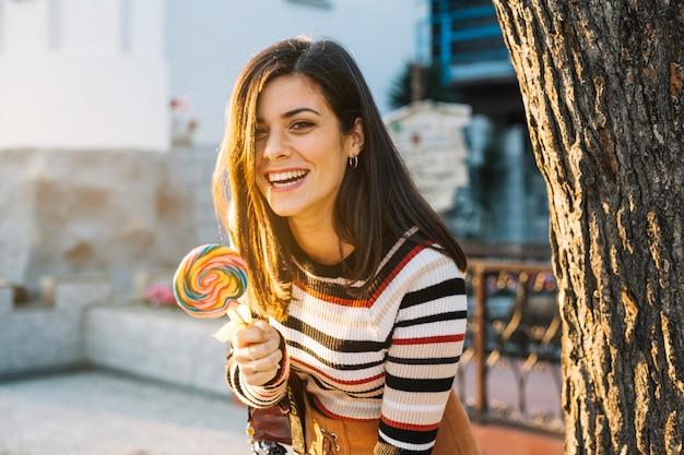 Ragazza ridendo con lecca-lecca colorata