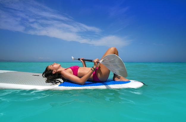 Ragazza rilassata sdraiata sulla tavola da surf paddle sup